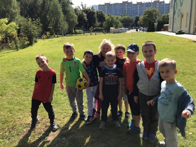 Uśmiechnięte dzieci na trawniku